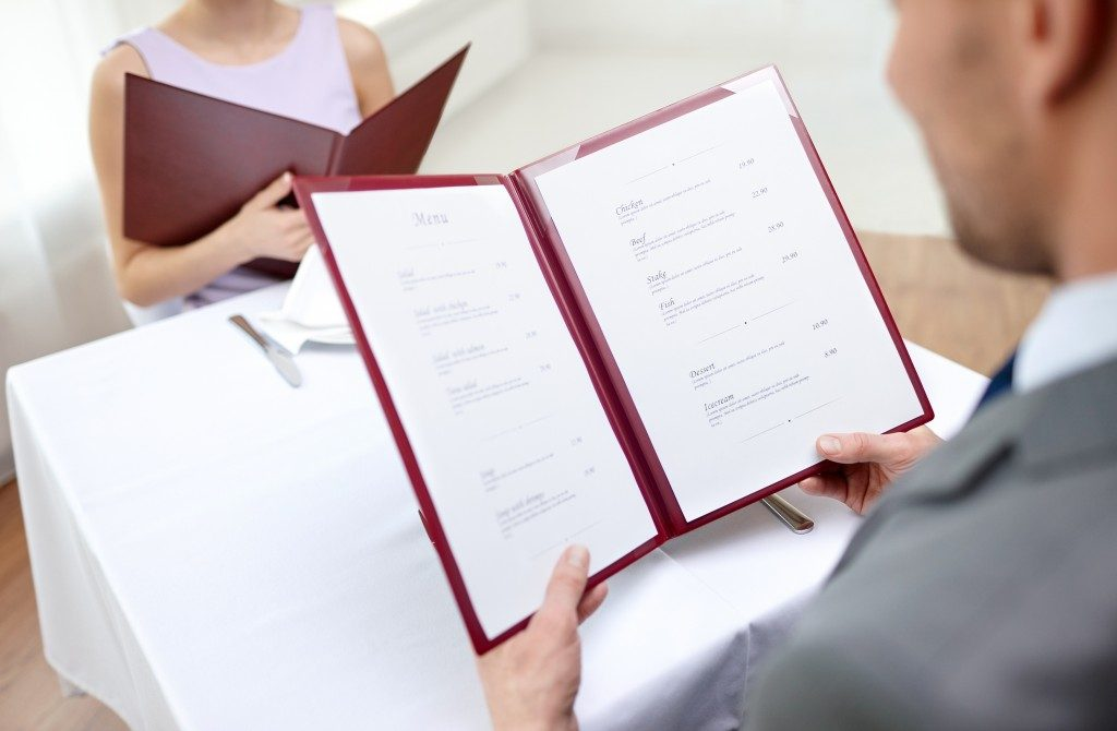 Browsing the menu of an expensive restaurant