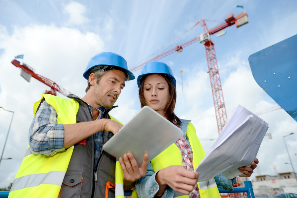 employees discussing a construction plan at a the site