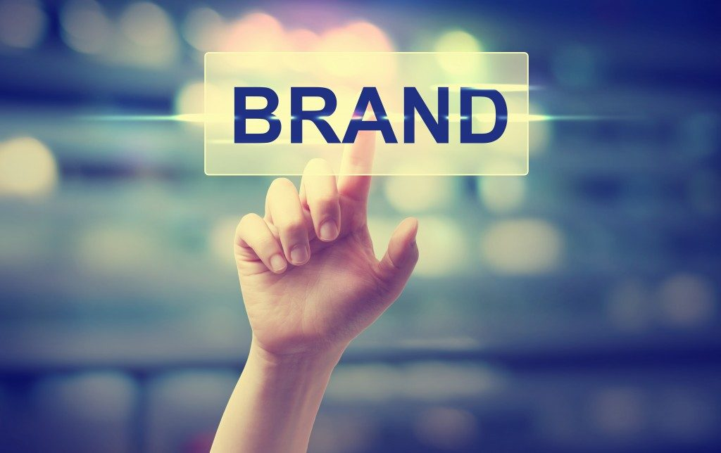 Hand pointing at the word BRAND