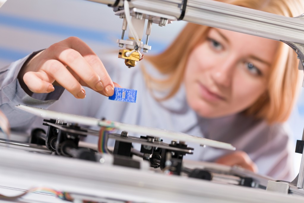 woman getting the product of a 3D printer