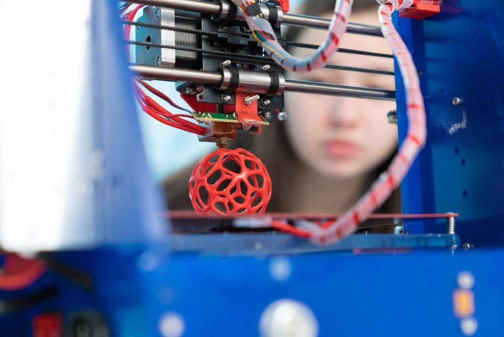 3D printer printing a red ball